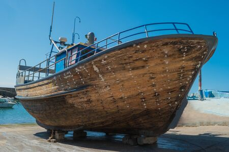 Repair of wooden boats in dry-dock. Boats are raised and waiting for repairs.