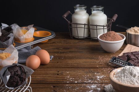 Homemade cooked muffins in a rustic setting with ingredients to cook on wooden table with copyspace. Stock Photo