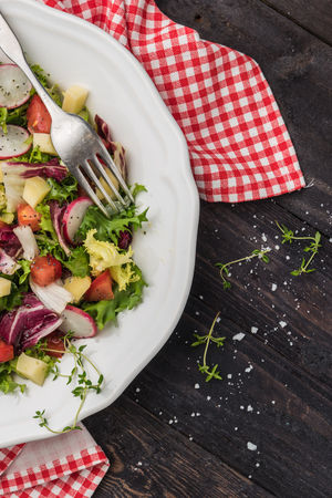 Fresh salad with mixed greens, radish, cheese and tomato in a plate on wooden background. Italian Mediterranean or Greek cuisine. Vegetarian vegan food. Fresh salad with mixed greens, radish, cheese and tomato in a plate on wooden background. Italian Mediterranean or Greek cuisine. Top view