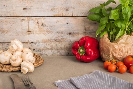 Fresh basil and other ingredients for Italian cuisine. Cherry tomatoes, basil and red pepper on wooden table for use as cooking ingredients