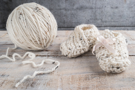 Knitting baby booties with bege yarn on wooden table Stock Photo