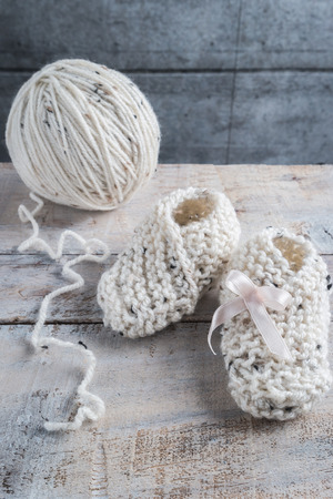 Knitting baby booties with bege yarn on wooden table Banco de Imagens
