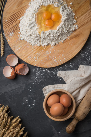 Top view eggs, dough, flour and rolling-pin on wooden table background. Preparation for making homemade ravioli pasta.