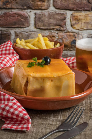 Traditional Portuguese snack food. Francesinha sandwich of bread cheese pork ham sausages with tomato beer sauce and french fries. With a glass of beer and potatoes. On wooden table. Copy space Imagens