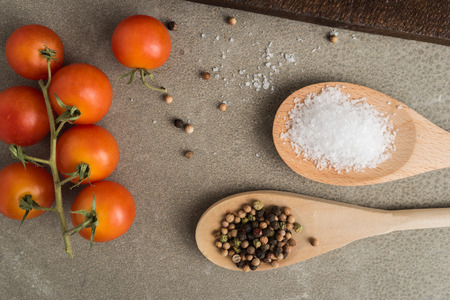 Top view of a bunch of natural cherry tomatoes, salt and pepper on cement background with copy space Stockfoto