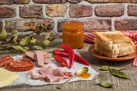 Traditional Portuguese snack food. Francesinha sandwich of bread cheese pork ham sausages with tomato beer sauce and french fries. With a glass of beer and potatoes. On wooden table. Copy space Stockfoto