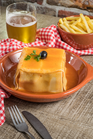 Traditional Portuguese snack food. Francesinha sandwich of bread cheese pork ham sausages with tomato beer sauce and french fries. With a glass of beer and potatoes. On wooden table