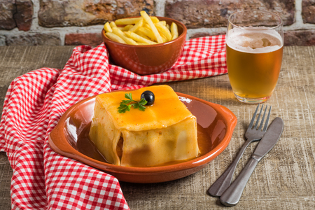 Traditional Portuguese snack food. Francesinha sandwich of bread, cheese, pork, ham, sausages, with tomato, beer, sauce and french fries. With a glass of beer and potatoes. On wooden table