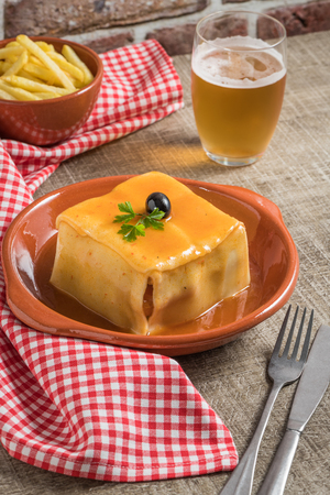 Traditional Portuguese snack food. Francesinha sandwich of bread, cheese, pork, ham, sausages, with tomato, beer, sauce and french fries. With a glass of beer and potatoes