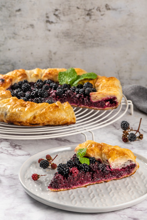 Blackberries pie with a slice on plate. Pie in summer with fresh picked wild blackberries
