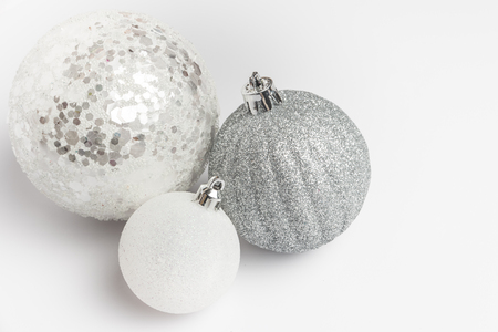 Festive glitter christmas balls decorations on metalic fabric texture. Seasonal winter holidays. Top view with copy space