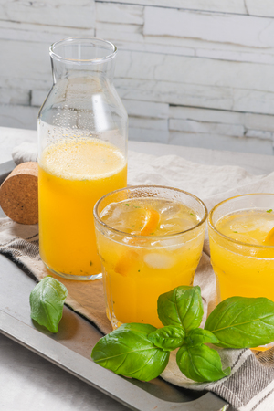 Homemade orange juice with ice cubes and basil leaves in glass on board Stockfoto