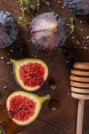 Fresh figs. Whole figs and sliced in half figs and thyme leaves on wooden cutting board. 写真素材