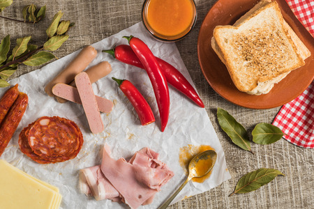 Ingredients for preparing the traditional portuguese snack food. Francesinha sandwich of bread, cheese, pork, ham, sausages, with tomato, beer, sauce and french fries. On wooden table. Top view Imagens