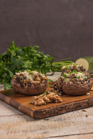 Mushroom caps stuffed with vegetables and cheese, baked in oven and garnished with a sprig of parsley. Mushroom appetizer on wooden board. Closeup