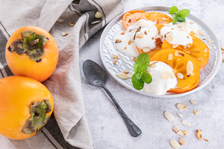 Sliced persimmon with yogurt and almonds. Healthy food concept on light background