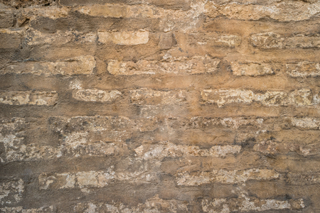 Old brick wall with cracks and scratches. Brick wall background. Distressed wall with broken bricks texture. House facade