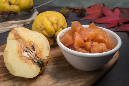 Quince fruits and marmelade in a ceramic bowl on table top Stockfoto