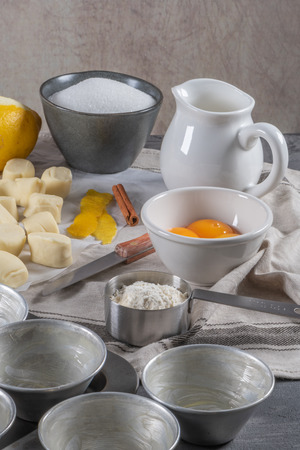 Ingredients for homemade baking portuguese egg tarts - flour, milk, water, egg, sugar, lemon, cinnamon, pastry and cake pan. Traditional portuguese dessert pastel de nata