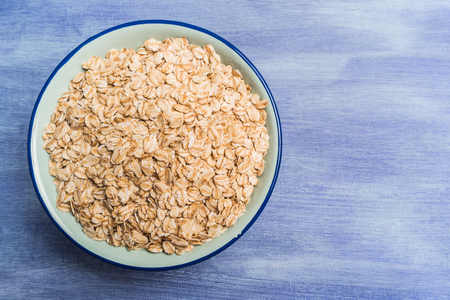 Oat flakes in a bowl on rustic textured background. Top view with copy space.