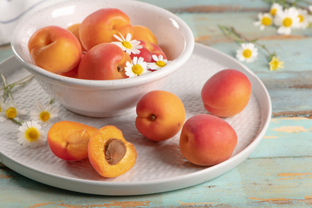 Delicious ripe apricots in a bowl on the wooden table. Close-up with apricots and daisy flowers
