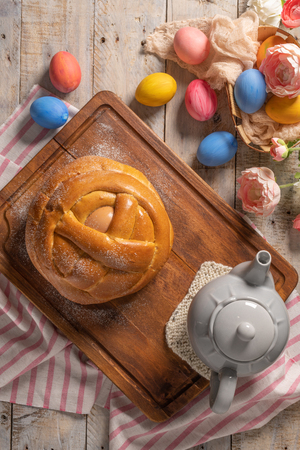 Portuguese traditional Easter cake. Folar with eggs on wooden table