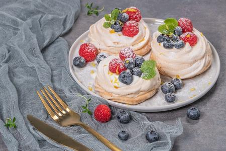 Mini pavlova cakes with fresh raspberries and blueberries
