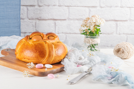 Portuguese traditional Easter cake. Folar with eggs on wooden table Standard-Bild