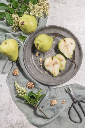Tasty pears with nuts. A table decorated with flowers and a plate of pears cut into the plate Reklamní fotografie