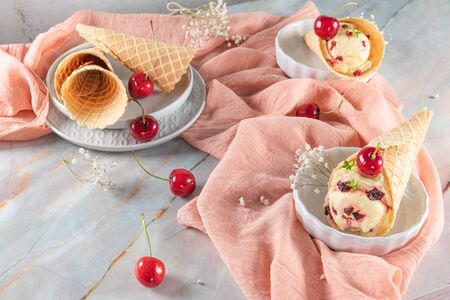 Traditional waffle cones with ice cream and cherry fruits on marble stone surface.