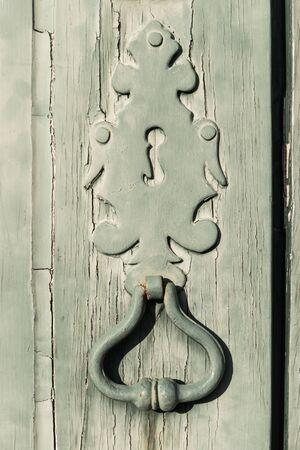 Old metal door handle knocker on a rough wooden background Reklamní fotografie