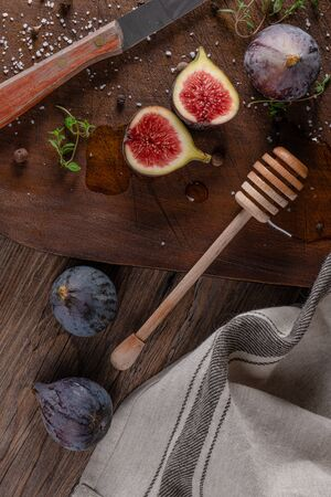 Fresh figs. Whole figs and sliced in half figs and thyme leaves on wooden cutting board