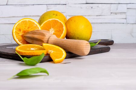 Slice of orange on wooden board with sharp knife. Fresh citrus orange fruits on cutting board for salad or juicing. Healthy eating, cooking, diet and summer concept