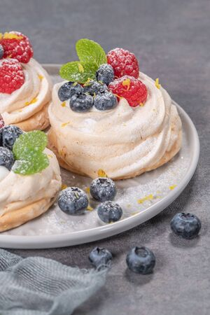 Mini pavlova meringue cakes with fresh raspberries and blueberries with mint leaves. Reklamní fotografie