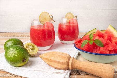 Fruity summer cold drink, homemade watermelon juice or smoothie served with lime and fresh mint leaves, light blue trendy background copy space Stockfoto