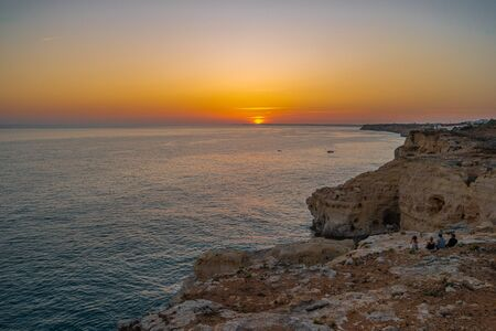 Friends seated on cliff and watching Sunset at Atlantic ocean coast, in Carvoeiro beach clifs, Algarve, Portugal Stock fotó