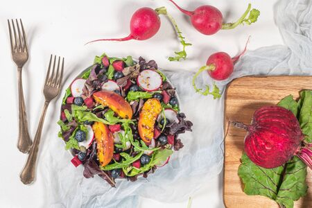 Fresh spring salad with rucola, lettuce, blueberries, radish, beet and slices of peach. White background with free text space. Top view.
