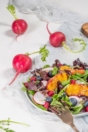 Fresh spring salad with rucola, lettuce, blueberries, radish, beet and slices of peach. White background with free text space.