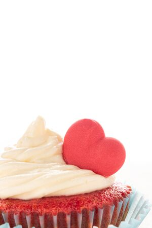 Red velvet heart cupcake with cream cheese frosting and a red heart for Valentines Day. Isolated on white background with copy space.
