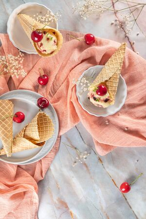 Traditional waffle cones with ice cream and cherry fruits on marble stone surface. Top view