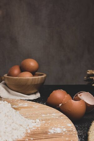 Eggs, dough, flour and rolling-pin on wooden table background. Preparation for making homemade ravioli pasta