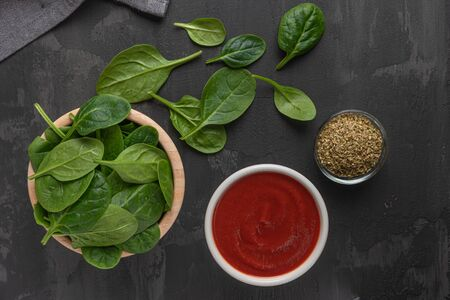 Italian cuisine. Mediterranean cuisine. Spinach leaves, tomato, oregano, tomato sauce and olives on table. Recipe Ingredients. Stok Fotoğraf