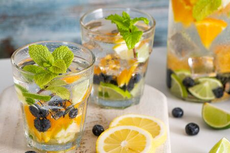 Summer healthy cocktails of citrus infused waters, lemonades or mojitos, with lime lemon orange blueberries and mint, diet detox beverages, in glasses on light background