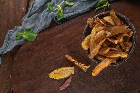 Top view of wooden cutting board on old wooden table top with tablecloth and sweet potato chips in a bowl Stockfoto