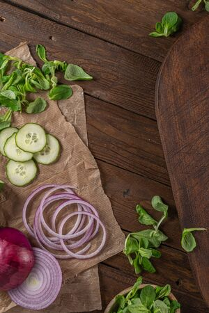 Top view of wooden cutting board on old wooden table top with tablecloth, sliced red onion and cucumber and corn salad