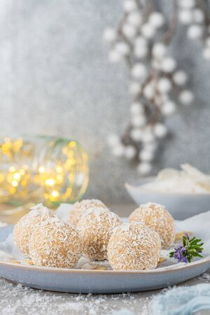 Homemade sweet white chocolate and coconut in a plate. Raffaello candy - snowball truffles on a Christmas table Stock fotó