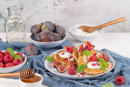 Pancakes with raspberries, figs, yogurt, coconut zest, honey and mint leaves on a plate