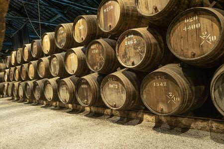 Fila de barriles de vino de madera de Oporto en la bodega de Oporto, Portugal.