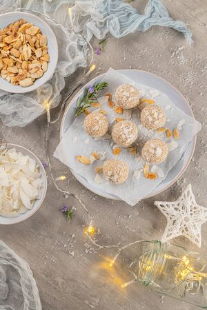 Homemade sweet white chocolate and coconut in a plate. Raffaello candy - snowball truffles on a Christmas table. Top view.
