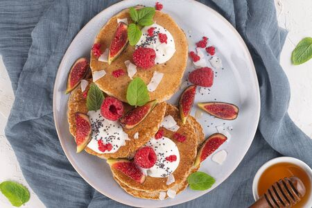 Pancakes with raspberries, figs, yogurt, coconut zest, honey and mint leaves on a plate.